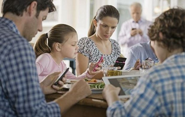 Family eating using smartphones